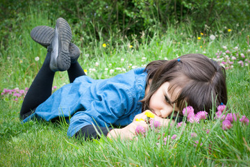 Sad little girl lying in the grass