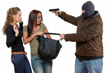 Bad guy is robbering a two young women with a gun