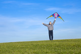 Happy man with a kite also holds a finger up