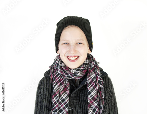 Smiling boy in a cap and a scarf. Youth fashion