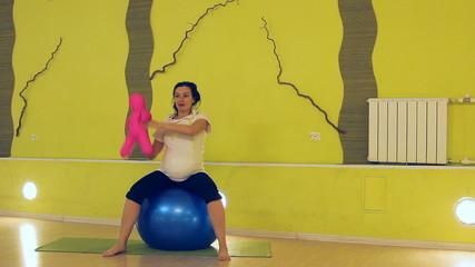 беременная женщина с куклой делает упражнения с мячом, йога