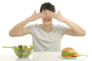 Young man holding in front a bowl of salad and a big hamburger.