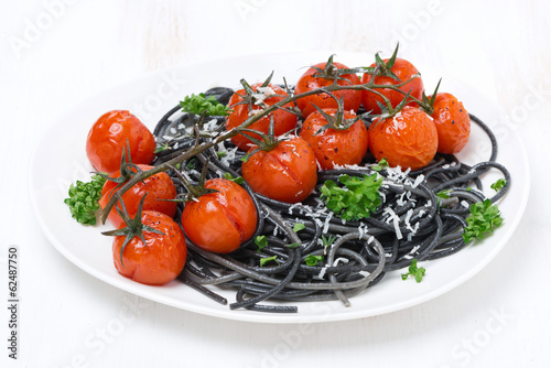 black spaghetti with baked tomatoes and parsley on the plate