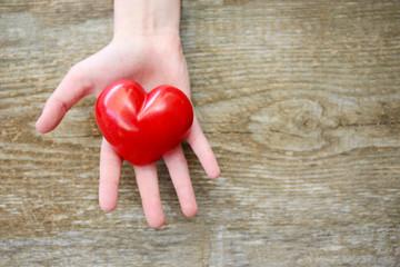 Kinderhand mit einem roten Herzen
