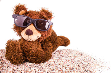 teddy bear with sunglasses on the sand