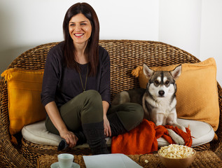 Beautiful woman relaxing in living room with Siberian Husky
