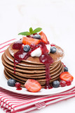 pancakes with cream and berries on a wooden table