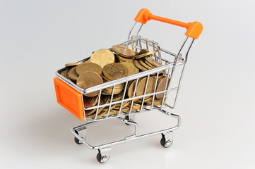 Shopping cart full of coins on gray