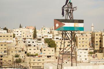 Rusty Jordan flag and Amman buildings view