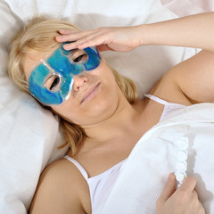 Frau liegt mit Kopfschmerz im Bett