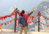 cheering woman hiker at peak of mountain huashan