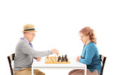 Mature couple playing chess seated at a table