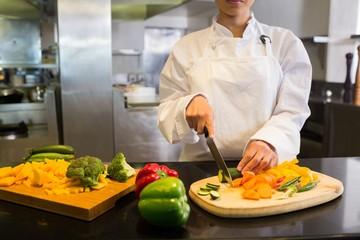 Female chef cutting vegetables in kitchen