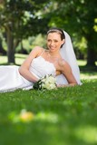 Happy bride lying on grass in park