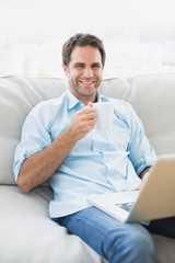 Happy man using laptop sitting on sofa having a coffee
