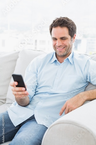 Cheerful man sitting on the couch sending a text with smartphone