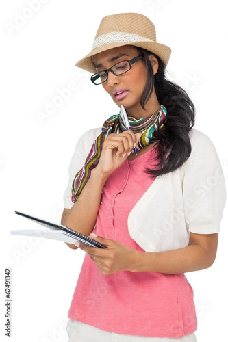 Serious cool young woman writing in notepad