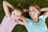 Happy mother and daughter lying on grass at park