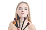 Beauty photo of girl with five makeup brushes.
