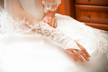 Closeup shot of bride putting on lace fingerless gloves