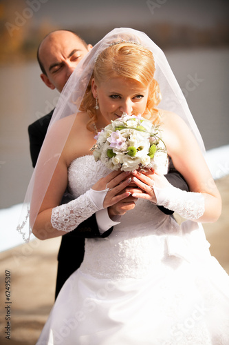 groom hugging beautiful bride that is smelling flowers