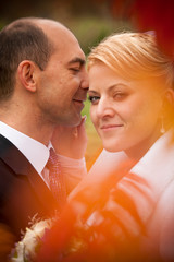 Closeup shot with orange flares of happy newly married couple
