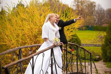 Portrait of handsome groom and bride looking at sky on bridge