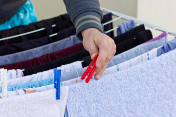 Young man drying clothes after laundry