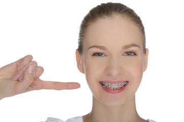 Smiling happy girl indicates braces on teeth