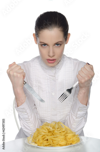 woman with fork, knife and spaghetti, sits