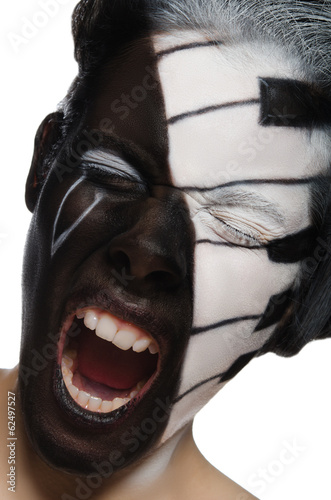 Portrait of screaming woman with face art as piano