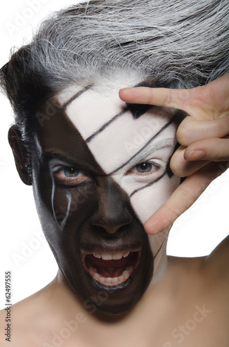 Screaming woman with face art and rock gesture