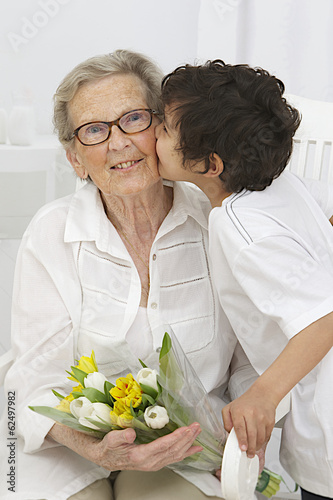 Happy grand mother and little son embracing with flowers