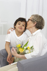 Happy grand mother and little son offering flowers