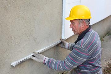 Worker placing aluminum batten for styrofoam insulation to wall