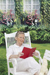 Senior woman relaxing in chair with novel  in her garden