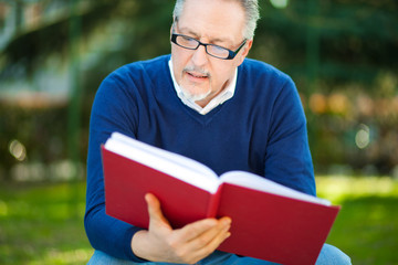 Mature man reading a book