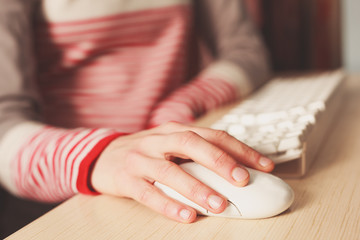 Closeup on young woman using computer mouse