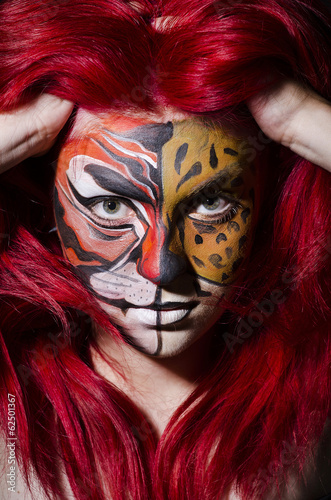 Woman with face painting in dark room