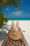 Woman at beach lying on chaise lounge