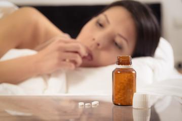 Frau im Bett nimmt Tabletten ein
