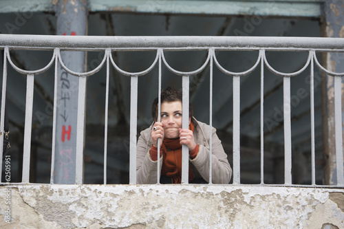Portrait of young woman behind the hand-rail