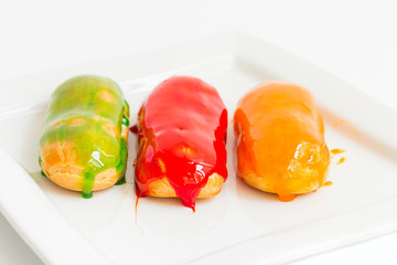 Eclairs with colorful caramel glaze
