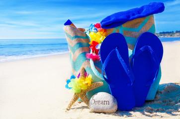 Beach bag with flip flops by the ocean