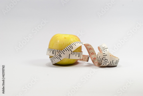 Apple and measuring tape isolated on white