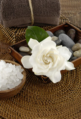 spa salt in bowl and gardenia and stones with towel  on mat