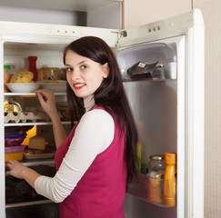 woman looking for something in refrigerator  at home