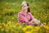 beautiful young girl with sunglasses in dandelion field