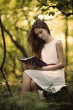 young beautiful girl with book in the forest