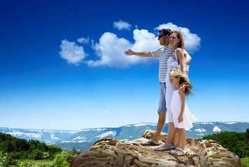 Family stay on the top of mountain, looking on the beautiful vie